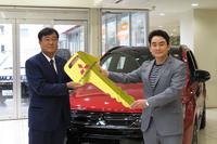 納車式には三菱自動車の益子 修社長も登場。野口氏に「アウトランダーPHEV」のキーを手渡した。