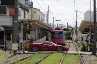 世田谷線と交差する「488GTB」。フェラーリはエンジンのターボ化や独自のアイドリングストップ技術「HELLE」で燃費向上に対応する。(photo:北畠主税)