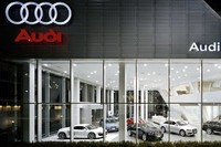夜の「Audi豊洲」。広いガラス面にアウディ車の姿が浮かぶ。