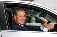 BMW530iのドライバーズシートでポーズを取るバレンタイン監督。ホントにクルマが好きそう。