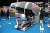 屋内展示会場に設置されていた安全運転支援システム体験シミュレーター。