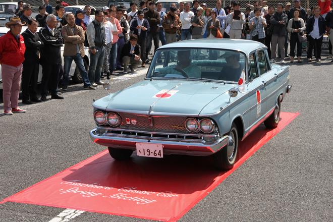 レッドカーペット上で紹介を受けた後にパレードにスタートする、特別展示車両の一台である1964年「プリンス・グロリア・デラックス」。東京オリンピックの際にJOC(日本オリンピック委員会)の公用車として提供されたヒストリーを持つ車両で、カタログにはないソリッドカラーのライトブルーで塗られている。