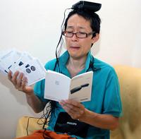 フィリップス製ビデオトランスミッターの説明書と格闘する筆者。