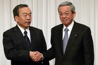 握手をするトヨタ自動車の内山田竹志取締役副社長(左)とマツダの山木勝治代表取締役副社長執行役員。