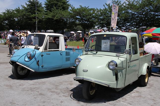 軽三輪トラックのライバル同士だった1964年「ダイハツ・ミゼットMP5」(右)と「マツダK360」(左)。バイクのように前輪の後方に空冷2ストローク単気筒エンジンを縦置きするシンプルなミゼットに対して、K360は空冷4ストロークVツインをキャビンと荷台の間にミドシップする凝った設計だった。