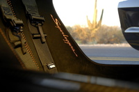 """薄いカーボンファイバーの一体型バケットシートに、薄いクッションが敷かれ、アルカンタラが貼られる。""""レーシィ""""の記号。"""