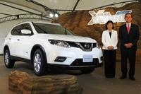 「日産エクストレイル ハイブリッド」と日産自動車の片桐隆夫副社長(右)、星野朝子専務執行役員(左)。