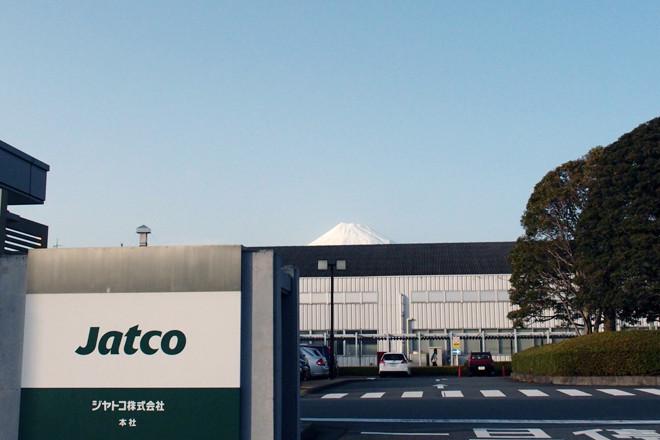 静岡県富士市にある、ジヤトコ本社の正面入り口。建屋の奥に、富士山の頂が見える(新幹線の最寄り駅である新富士駅から同社までは、どこでも富士山が拝める。ぜいたくなものだ)。 現在、同社の生産拠点は、日本のほかに、中国、タイ、メキシコなど。これら海外工場の強化が、円高に苦しむ日本の自動車メーカーの、海外生産拡大のカギを握っている。現在、トランスミッションの生産台数は国内がほとんどだが、2012年を境に海外生産の傾向は急速に強まり、その比率は、2014年には半々、2017年には3:7と、逆転することが見込まれている。