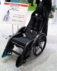 フレームはカーボン! 4点式シートベルトを備える、童夢製の車いすシステム。