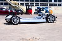 「モデルS」の土台となるランニングコンポーネント。向かって右側が車体の前方。バッテリーはホイールベース間の床下に敷き詰められるため、オーバーハングに重量物はない。駆動用モーターは後輪の間に搭載されている。前後の重量配分は48:52と理想的。