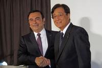 握手を交わす日産のカルロス・ゴーン社長兼最高経営責任者(写真左)と、三菱自動車の益子 修取締役会長兼CEO(同右)。