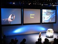 開発責任者の門田英稔氏が、スマートフォンを使ってショールームにあるリーフに充電しているところ。