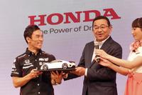 報告会では、本田技研工業の八郷隆弘代表取締役社長(写真右)も姿を見せ、佐藤の勝利を祝福。記念の品として、スーパースポーツ「NSX」を贈呈した。「これはミニチュアですが、ちゃんと実物を差し上げます」という社長のコメントに、佐藤も大笑い。