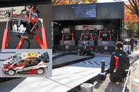 TGRとタミヤのコラボによる「グラビティ・ラリー」。シミュレーターに乗り、ヘッドマウントディスプレイを装着した参加者が、カメラ付きの10分の1のRCカーを、ジャンプ台もあるコースで走らせる。