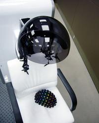 座面に置かれた帽子が、計測用センサー。写真下のように装着したあと、無数のケーブルで計測装置に繋がれる。