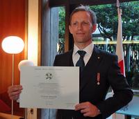 賞状を手にするクインタレッリ氏。左胸を飾るのが、今回授与された「イタリア共和国 連帯の星勲章」。日本のスポーツ界ではほかに、サッカーの元日本代表でイタリアのセリエAでも活躍した中田英寿氏が受勲している。