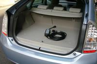 荷室の床下には、ノーマルのニッケル水素バッテリーに比べ、体積で3倍、容量で4倍勝るリチウムイオンバッテリーがおさまる。結果、ラゲッジスペースを1割侵食。フロアボード下のエクストラスペースも失われた。(写真中央のコード類は、充電用の専用アダプター)