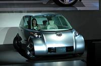 """燃料電池ハイブリッド車「Fine-X」。前後タイヤがいつもと違う位置を向いている。 左右のドアは巨大なガルウィング、シートは車外に出て乗員を""""お出迎え""""する。"""
