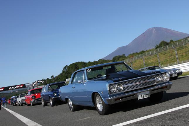 雲ひとつなく晴れわたった青空に向かってそびえ立つ富士山をバックに出走を待つ、ナンバー付き車両で争われるストリートクラスのマシン群。先頭は1965年「シボレー・シェベル」。コンパクトとフルサイズの間のインターミディエート(中間サイズ)である。