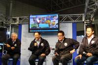 壇上に並んだ、(写真左から)成瀬弘氏、モリゾウ氏、TOM'Sの舘信秀代表、そしてレーシングドライバーの飯田章氏。 会場の様子は、ネット上の仮想未来都市空間「トヨタメタポリス」上でも中継されて、一同思わず照れ笑い。