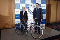 左から日直商会の日向八郎代表取締役、ミシュランマンを挟んで日本ミシュランタイヤのベルナール・デルマス代表取締役社長。