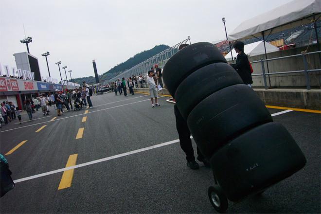 """9月19日土曜日、ツインリンクもてぎ――ピットでは、朝から""""タイヤ男""""がお出迎え。どのチームも本番をひかえて準備に余念がない。"""