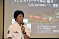 体験会場で「CAN-Gateway ECU」について説明する、「トヨタ86」のチーフエンジニア 多田哲哉氏。実車の走行データを身近な端末上で再現することにより、リアルとバーチャルを交えたモータースポーツや運転上達のための練習ができるなど、クルマの楽しみ方が広がるという。