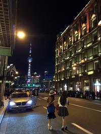 上海随一のホテル「和平飯店」前にて。ファッショナブルな小姐(お姉さん)の向こうで、最新スマートフォンを操る若者が上海ナンバーのBMWに乗り込んだ。