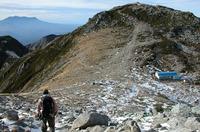 中岳の頂を越え、眼下に小屋が見えた。さあ、あれが今晩の宿だ、と思いきや……。向こう側にかすんで見えるのは御嶽山。