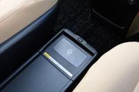 ハイブリッド車の1列目シート間には、「おくだけ充電」機能を持つトレイが配される。ワイヤレス充電の規格Qi(チー)に対応するスマートフォンやデジタルカメラを、トレイに乗せるだけで充電することができる。トレイそのものの高さをウォークスルーできる程度に抑えたのも、開発のポイントだという。