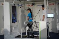 まひした脚にロボット脚を装着して、トレッドミル上でリハビリを行う。