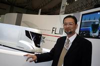 いすゞデザインの中尾博さん。後方はコンセプト「FL-III」ディーゼル+インホイールモーターを想定。