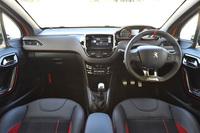 「プジョー208GTi」のインテリア。ステアリングホイールやシート、メーター、ドアパネルに赤いアクセントが添えられるほか、テップレザーのダッシュボードや革巻きのサイドブレーキカバーには赤いステッチが施される。