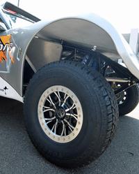 """マシンの骨格をなすパイプフレームと、サスペンショントラベルの長さがよくわかるカット。タイヤのサイズはLT315/70R17で、""""LT""""はライトトラック=トラック用を示す。"""
