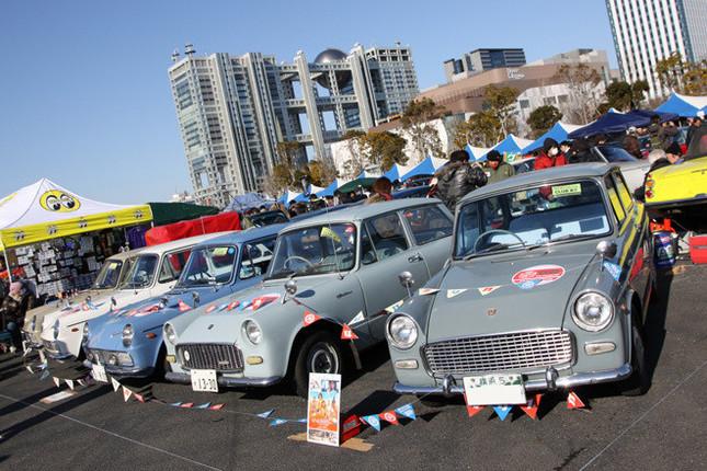 4台のセダンと1台のトラック、計5台を並べた「パブリカオーナーズクラブ」のクラブスタンド。1961年にデビューした「パブリカ」は、公募により決定された「public」と「car」の造語である車名を持つ、空冷フラットツインを積んだトヨタ初の大衆車。右端の「横浜5」のシングルナンバー付きは公開中の『ALWAYS 三丁目の夕日'64』出演車両で、その隣は希少な「スタンダード」の、しかも超希少な「トヨグライド」(2段AT)仕様。