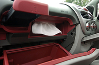 """実はiの収納スペースはそれほど多くない。助手席のグローブボックスやドリンクホルダーなどがあるが、ATシフター前方、インパネ真下にある底の浅い収納はちょっと意味不明。うかつに物を置いてペダルとフロアの間に転がり落ちたりしたら……。フロアではなくコラムシフトにして前席間のスペースを稼いだほうがよかったのでは?クリックすると、""""隠れティッシュボックス""""が登場。これは便利。"""