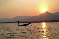 脚でオールを漕いでボートを操作し漁をする地元の漁師とインレー湖の夕暮れ。