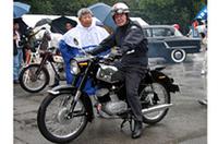 2ストローク単気筒エンジンを積んだスズキの「1959年式コレダST-6A」に跨がっているのは、日本人として初めてマン島TTレースに優勝(63年・50ccクラス)した往年の名ライダー、伊藤光夫氏。