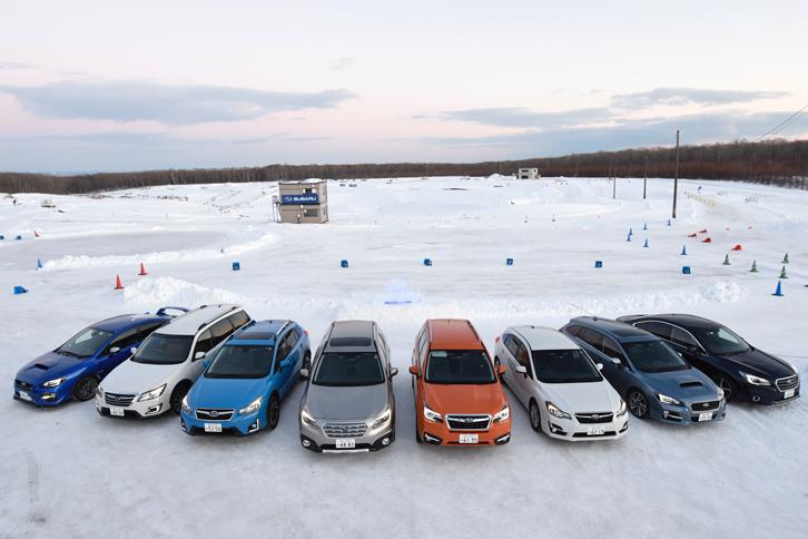 雪景色の新千歳モーターランドにずらりと並んだ、試乗用のスバル車。写真左から、「WRX STI」「エクシーガ クロスオーバー7」「XV」「レガシィアウトバック」「フォレスター」「インプレッサスポーツ」「レヴォーグ」「レガシィB4」。水平対向4気筒エンジンを搭載する4WD車である点は全車共通だが、採用されている4WDシステムのタイプは、4つ(アクティブトルクスプリットAWD/不等&可変トルク配分電子制御のVTD方式AWD/ドライバーズコントロールセンターデフ付きのDCCD方式AWD/ビスカスLSD付きセンターデフ方式AWD)に大別される。