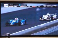 会場で放映された、今回のインディ500を振り返る映像から。レース終盤、首位に立った佐藤(写真左)が、優勝に向かってラストスパートをかける。