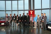 記念撮影を行う、9組のオーナーと、テスラモーターズのイーロン・マスクCEO(右から7人目)およびテスラモーターズジャパンの樺山資正 代表執行役員社長(右から6人目)。