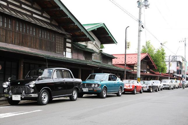 このイベントのために一般車両は通行止めとなった「こみせ通り」に並んだ参加車両。先頭から初代「ダットサン・ブルーバード」、4代目「トヨペット・コロナ ハードトップ」、「ロータス・ヨーロッパ」……。