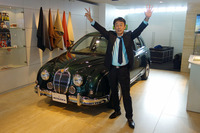 """光岡自動車の光岡章夫代表取締役社長。手の指で""""25""""を表現している。"""