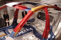 カットモデルで赤く示される部分が、今回話題となっている1.2GPa級の高成形性超ハイテン材。以下強度の順に、オレンジの部分が780〜980MPa、青い部分は440〜590MPa、地色(無色)の部分は200〜300MPa程度の「軟鋼」を示す。