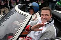 2000GTボンドカーの助手席に乗り、オープニングパレードに向かうラルフ。ステアリングを握るのは、かつて2000GTや「トヨタ7」を駆って活躍した元トヨタワークスの大坪善男氏。日本を舞台にした映画『007は二度死ぬ』のロケ撮影で、実際に2000GTボンドカーのスタントドライバーを務めたのも、じつはこの大坪氏だった。