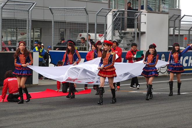 「TOYOTA GAZOO Racing FESTIVAL 2013」の開会式におけるひとこま。大きなフラッグを持って現れたのは、人気アイドルグループ「AKB48」のメンバー6人。これは当日のサプライズであったらしく、グランドスタンドにはどよめきが……。