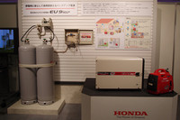 携帯型発電機による、災害時の発電イメージ。家庭用LPガスのボンベ(写真左)から専用ガス供給ボックス(写真中央)を介してLPガスを確保。それを燃料に電気を作り出す。