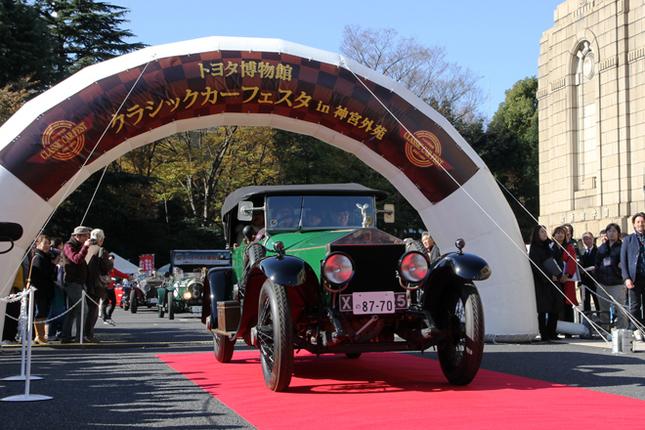 午前10時からのオープニングセレモニー終了後、恒例の公道パレードへと出発。先導車に続くカーナンバー1は、1919年「ロールス・ロイス・シルバーゴースト40/50HPアルパインイーグル」。白洲次郎のベントレーや吉田 茂のロールス・ロイスをはじめ、貴重なロールスとベントレーを動態保存しているワクイ・ミュージアムの所蔵車両である。