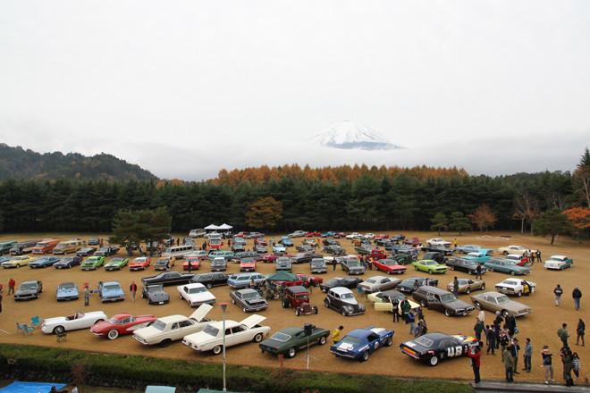 雪を頂いた富士山が見下ろす、すっかり黄色くなった芝生広場に集まった、およそ120台のアメリカン・ヒストリックカー。