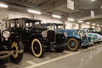 バックヤードにずらりと並ぶ収蔵車。バックヤードは普段は公開されていないが、それでも収蔵車のなかには解説パネルが添えられているものがあった。ちなみに手前のモスグリーンの車両は「ピアスアロー・シリーズ36(1927年・アメリカ)」、その隣のブルーの車両は「キャデラック・シリーズ452A(1931年・アメリカ)」。